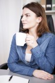Observant young businesswoman drinking coffee — Stock Photo