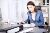 Hardworking businesswoman sitting writing a report — Stock Photo