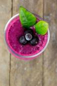Milkshake with black currants in a glass against the background of wooden boards — Stock Photo