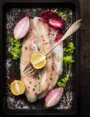Raw fish with herb, spices and fork on black old backing tray, top view — Stock Photo