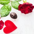 Valentines day border with big red heart, roses and  chocolate on white wooden background — Stock Photo #66133025