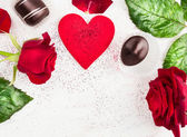 Love heart background with red roses and chocolate pralines , valentine — Zdjęcie stockowe