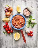Salsa de tomate con atún en lata en rústica olla con verduras y especias, fondo blanco de madera, vista superior — Foto de Stock