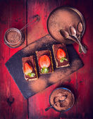 Tiramisu with strawberries and Chocolate powder, composing on red wooden background, top view — Stock Photo