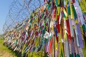 Lots of colorful tapes dedicated to reunification are hang at the fence at Korean Demilitarized Zone — Stock Photo