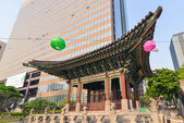 Contrast of an little traditional building and modern huge office building next to it in Seoul — Stock Photo