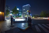 People at the sidewalk in the lights of night illumination in Seoul downtown — Stock Photo