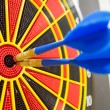 Two darts in bullseye of dartboard — Stock Photo #52568971