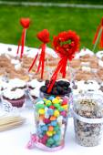 Colorful sweets with hearts on the banquet table — Stock Photo