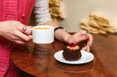 Female hands closeup hold a cup of coffee and cake — Stock Photo