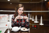 Young women in a plaid shirt drinking tea in a cafe — Foto de Stock