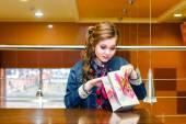 美丽的女孩在一家咖啡馆,看在礼品袋 — 图库照片