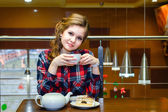 Young women in a plaid shirt drinking tea in a cafe — ストック写真