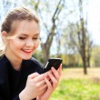 Woman with unkempt hair looking into smartphone smiling — Stock Photo #70730983