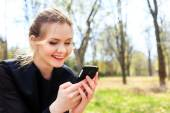 Woman with unkempt hair looking into smartphone smiling — Stock fotografie