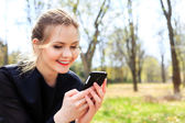 Woman with unkempt hair looking into smartphone smiling — Foto de Stock