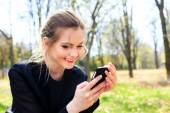Happy girl with disheveled hair looking into smartphone smiling — Stock Photo