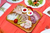Cold cuts on wooden plate on banquet table — Foto Stock