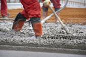 Workers in red boots with rake leveled the concrete — Stock Photo