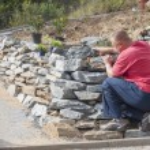 Gardener builds a stone wall, garden preparation, architect proposes Supplies — Stock Photo #54657583
