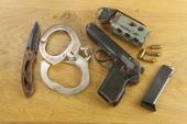 Firearm lying on the table, metal police handcuffs — Stock Photo