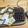 The concept of cybercrime. Criminal activity performed by computers and the Internet. Valid banknotes euro and the Czech koruna. Arrest cybercriminals, metal handcuffs and computer keyboard. — Stock Photo #76418383