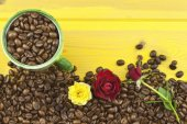 We love coffee. Roses resting on the coffee. Coffee beans, poured out on Yellow wooden table. Background for your text. — Stockfoto