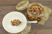 Jar of honey and nuts. Sweet treat for snacking. Pickled walnuts in honey. The ingredients for the sweet taste of dessert. — Stock Photo
