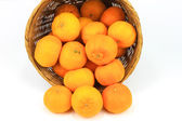 Pile of mandarin oranges in rattan basket — Stock Photo