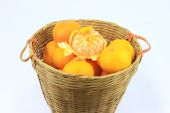 Pile of mandarin oranges in rattan basket — Stock Photo