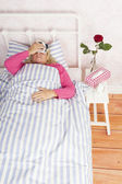Woman lying in bed with headache — Stock Photo
