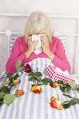 Woman in bed with roses and tissues — Stock Photo