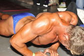 Male bodybuilding contestant doing warming up pushups — Stock Photo