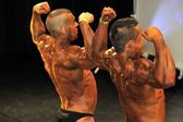 Male bodybuilding contestant showing his back double biceps pose — Stock Photo
