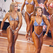 Female bikini fitness contestants showing their best in a lineup — Stock Photo