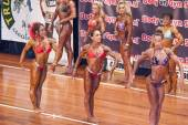 Female bodybuilders show their side chest post on stage — Stock fotografie