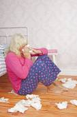 Sick woman sitting next to bed — Stock Photo