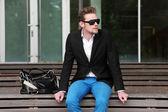 Man sitting outside sunglasses — Stock Photo