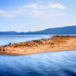 Lone small sandy island in the middle of blue sea — Stock Photo #70204649