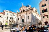 DUBROVNIK, CROATIA - APRIL 10: Tourists enjoy the terraces of restaurants in the old town of Dubrovnik in front of the Church of St. Blaise on April 10, 2015. — Stock Photo