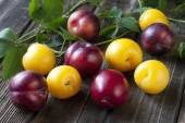 Fresh plums on wooden table — Stock Photo
