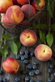 Fresh Peaches  and Nectarines  with green leaves in a basket on a wooden board — Stock Photo