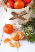 Christmas still life with mandarines and pine brunches — Stock Photo