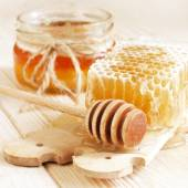 Honey in jar with honeycomb and wooden spoon — Stok fotoğraf
