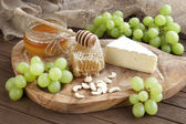 Cheese camembert with honey and nuts served with grape — Stock Photo