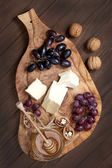 Cheese, grape and honey on wooden board — Foto Stock