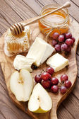 Cheese, grape and honey on wooden board — Stock fotografie