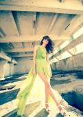 Beautiful model in green dress posing in grunge location  — Stock Photo