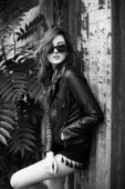 Pretty teenage girl posing outdoors in leather jacket against gr — Stock Photo