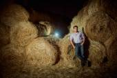 Handsome caucasian young man in the hay barn — Stock Photo